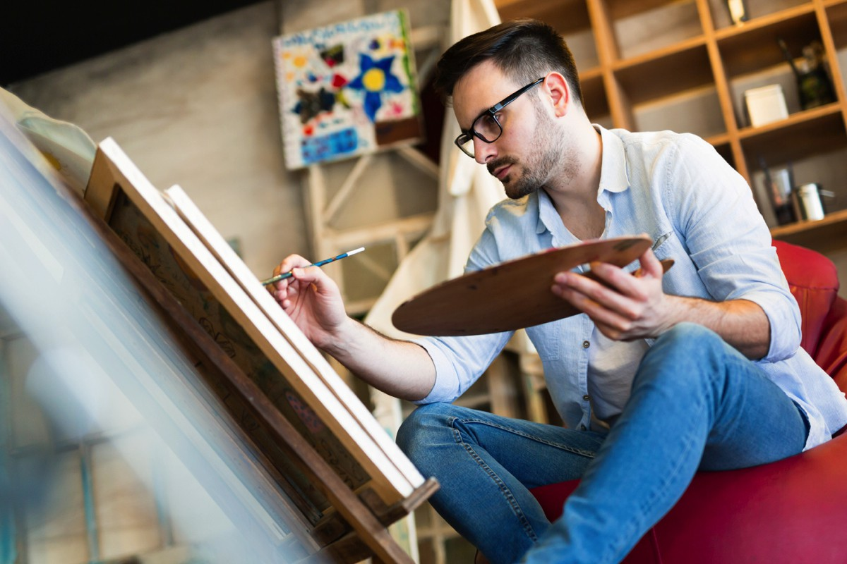 young-man-painting-on-canvas-D7Z5FH3