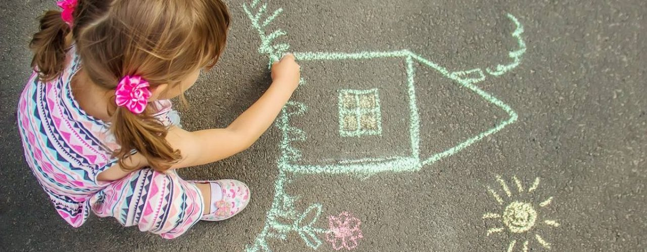The child draws the house with chalk on the asphalt. Selective focus. draw.