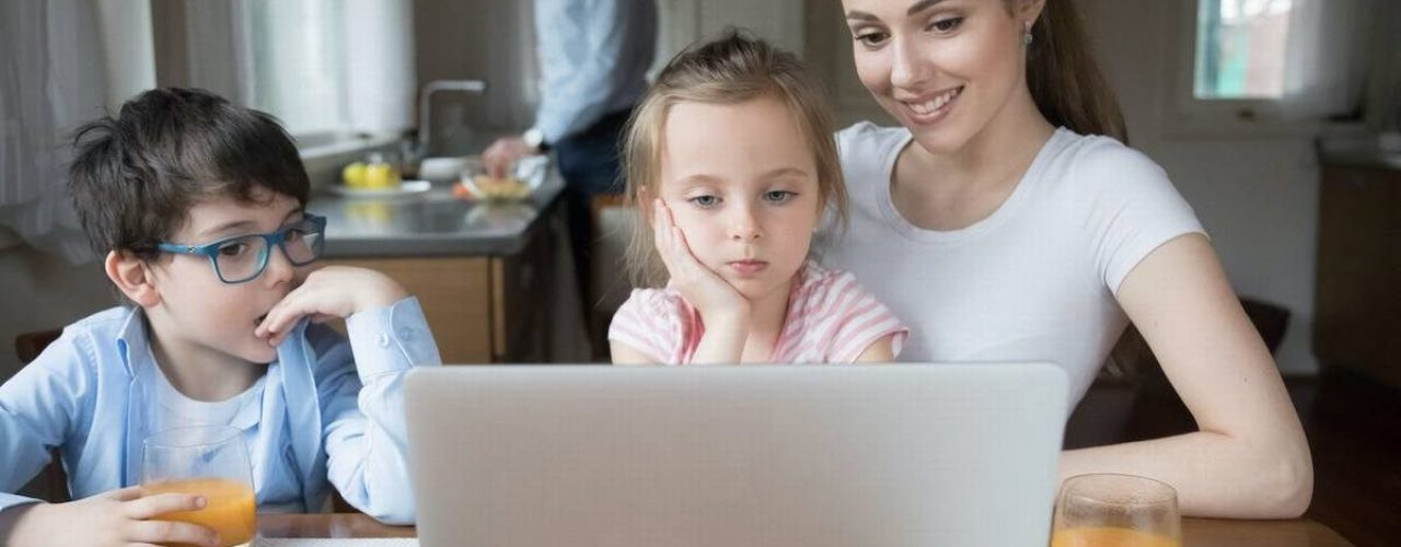 Mother showing cartoon on computer for children while father cooking. Family having fun, relax, leisure time on weekend at home. Wife entertaining kids. Gadget addiction concept, bad eyesight problem