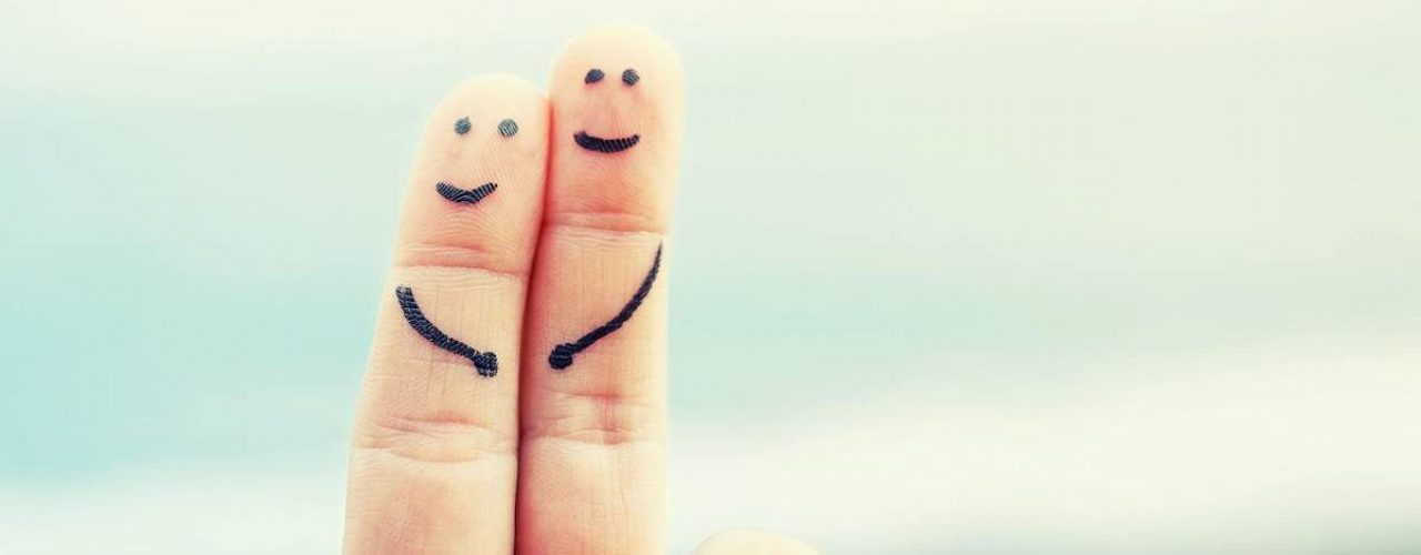Happy couple is symbolized by two fingers with painted smiley against the background of the sea. Romantic image